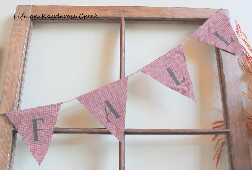 Fall DIY Projects - Stencils are used to spell out FALL on this cute pennant. What a great way to utilize this unworn shirt and create budget friendly, one of a kind fall decor.